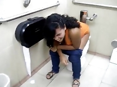 Sexy latina squatting in the public bathroom
